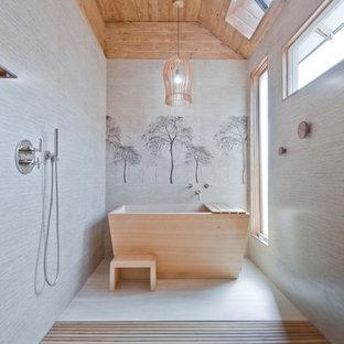 Inredning av ett asiatiskt badrum, med ett fristående badkar, en kantlös dusch, grå kakel, grå väggar, beiget golv och med dusch som är öppen