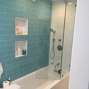 Diseño de cuarto de baño principal, moderno, de tamaño medio, con armarios con paneles lisos, puertas de armario blancas, bañera exenta, baldosas y/o azulejos azules, baldosas y/o azulejos de vidrio, paredes blancas y suelo de baldosas de cerámica