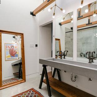 Imagen de cuarto de baño urbano con armarios abiertos, puertas de armario de madera oscura, paredes blancas, lavabo de seno grande, suelo gris, encimera de cemento y encimeras grises