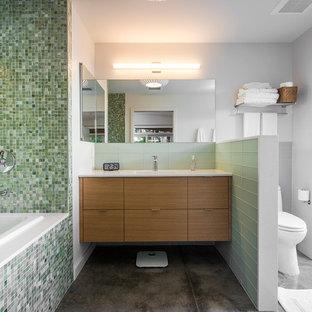 Diseño de cuarto de baño vintage con armarios con paneles lisos, baldosas y/o azulejos verdes, baldosas y/o azulejos en mosaico, bañera encastrada, ducha abierta, lavabo integrado, paredes blancas, suelo de cemento y puertas de armario de madera oscura