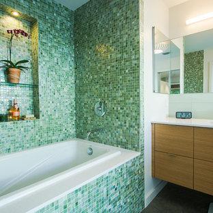 Modelo de cuarto de baño principal, retro, con armarios con paneles lisos, puertas de armario de madera clara, bañera empotrada, baldosas y/o azulejos verdes, baldosas y/o azulejos en mosaico, paredes blancas y suelo de cemento