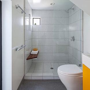 Modelo de cuarto de baño principal, actual, pequeño, con armarios con paneles lisos, sanitario de una pieza, baldosas y/o azulejos blancos, paredes blancas, suelo de cemento, lavabo tipo consola, puertas de armario naranjas, ducha esquinera, baldosas y/o azulejos de cerámica, encimera de cuarzo compacto, suelo gris, ducha abierta y encimeras blancas