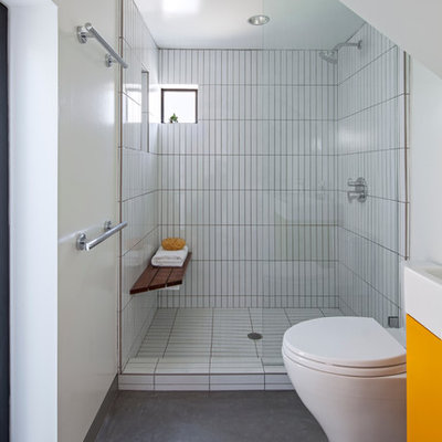 Small trendy master white tile and ceramic tile concrete floor and gray floor bathroom photo in Los Angeles with flat-panel cabinets, a one-piece toilet, white walls, a console sink, orange cabinets, quartz countertops and white countertops