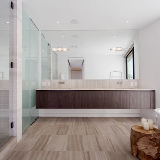 Bathroom - mid-sized eclectic master light wood floor and brown floor bathroom idea in Los Angeles with flat-panel cabinets, dark wood cabinets, white walls, an undermount sink, quartz countertops, a hinged shower door and beige countertops