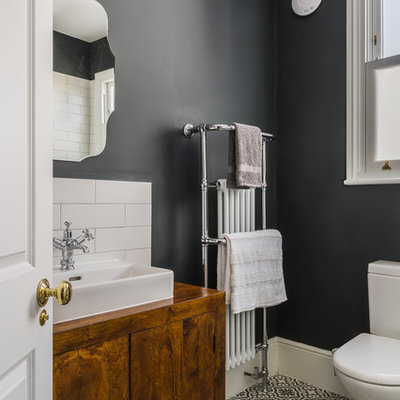 Inspiration for a small timeless ceramic tile bathroom remodel in London with flat-panel cabinets, dark wood cabinets, a one-piece toilet, gray walls and a vessel sink