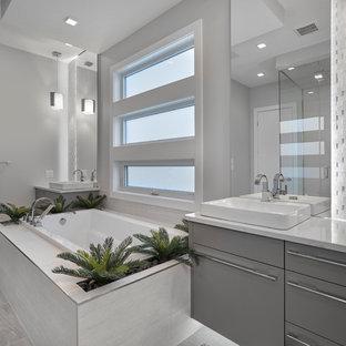 エドモントンのコンテンポラリースタイルのおしゃれな浴室 (フラットパネル扉のキャビネット、グレーのキャビネット、ドロップイン型浴槽、ダブルシャワー、グレーのタイル、磁器タイル、オレンジの壁、磁器タイルの床、ベッセル式洗面器、珪岩の洗面台) の写真