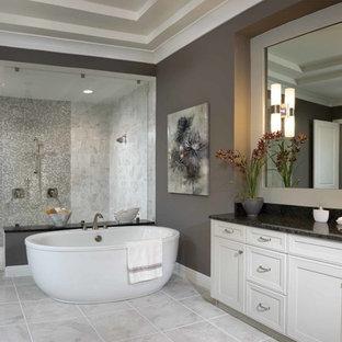 Ejemplo de cuarto de baño principal, clásico renovado, con armarios con paneles empotrados, puertas de armario blancas, bañera exenta, ducha doble, baldosas y/o azulejos grises, paredes grises, lavabo bajoencimera y ducha con puerta con bisagras