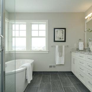 Imagen de cuarto de baño de estilo de casa de campo con armarios estilo shaker, puertas de armario blancas, bañera exenta y baldosas y/o azulejos grises