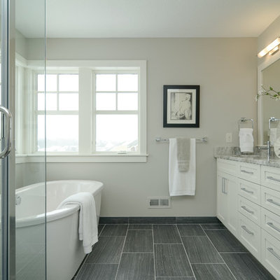 Freestanding bathtub - cottage gray tile freestanding bathtub idea in Minneapolis with shaker cabinets and white cabinets