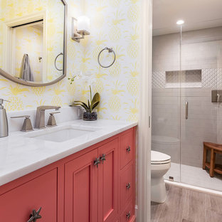 Inspiration for a beach style 3/4 bathroom with recessed-panel cabinets, red cabinets, an alcove shower, yellow walls, an undermount sink, grey floor, a hinged shower door and white benchtops.