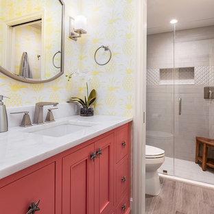 Ejemplo de cuarto de baño con ducha, costero, con armarios con paneles empotrados, puertas de armario rojas, ducha empotrada, paredes amarillas, lavabo bajoencimera, suelo gris, ducha con puerta con bisagras y encimeras blancas
