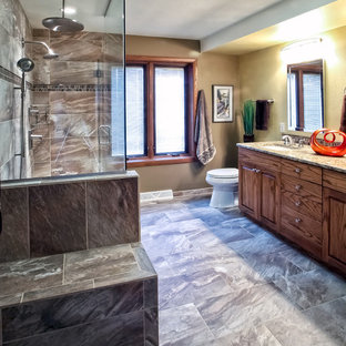 Mid-sized transitional 3/4 brown tile and stone tile porcelain floor corner shower photo in Other with an undermount sink, flat-panel cabinets, medium tone wood cabinets, limestone countertops, a two-piece toilet and brown walls