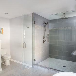 Ejemplo de cuarto de baño principal, tradicional renovado, grande, con lavabo bajoencimera, armarios con paneles empotrados, puertas de armario de madera en tonos medios, encimera de granito, bañera exenta, ducha empotrada, sanitario de dos piezas, baldosas y/o azulejos grises, baldosas y/o azulejos de porcelana, paredes grises y suelo de baldosas de porcelana