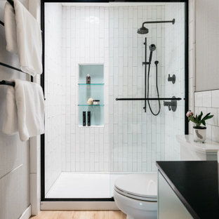 Design ideas for a small contemporary 3/4 bathroom in Los Angeles with flat-panel cabinets, turquoise cabinets, an alcove shower, a two-piece toilet, white tile, porcelain tile, white walls, vinyl floors, a vessel sink, granite benchtops, a sliding shower screen, black benchtops, a niche, a single vanity, a floating vanity and wallpaper.