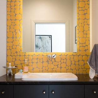 Imagen de cuarto de baño con ducha, moderno, extra grande, con puertas de armario negras, baldosas y/o azulejos amarillos, lavabo encastrado, armarios con paneles lisos, bañera encastrada, combinación de ducha y bañera, sanitario de una pieza, baldosas y/o azulejos de cerámica, paredes blancas y encimera de granito