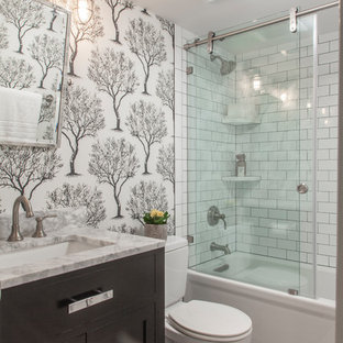 Small classic shower room in DC Metro with shaker cabinets, black cabinets, an alcove bath, a two-piece toilet, white tiles, metro tiles, vinyl flooring, a submerged sink, marble worktops, grey floors, a sliding door, grey worktops, a shower/bath combination and white walls.