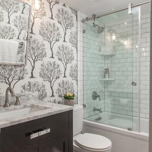 Modelo de cuarto de baño con ducha, tradicional renovado, pequeño, con armarios estilo shaker, puertas de armario negras, bañera empotrada, sanitario de dos piezas, baldosas y/o azulejos blancos, baldosas y/o azulejos de cemento, suelo vinílico, lavabo bajoencimera, encimera de mármol, suelo gris, ducha con puerta corredera, encimeras grises, combinación de ducha y bañera y paredes blancas