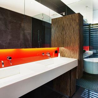 Immagine di una stanza da bagno design con vasca freestanding, doccia a filo pavimento, piastrelle arancioni, lastra di vetro, ante lisce, ante in legno bruno, bidè, pareti nere, pavimento in gres porcellanato, lavabo integrato, pavimento nero e doccia aperta