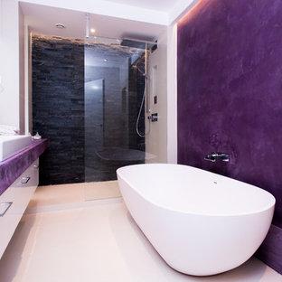 Immagine di una grande stanza da bagno padronale design con vasca freestanding, doccia aperta, WC sospeso, piastrelle nere, piastrelle in pietra, pareti viola, pavimento con piastrelle in ceramica e lavabo a consolle