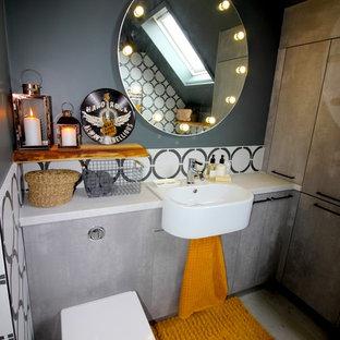 Immagine di una piccola stanza da bagno industriale con ante lisce, ante grigie, pareti grigie, top bianco, WC sospeso, pistrelle in bianco e nero, piastrelle multicolore, lavabo sospeso e pavimento beige