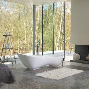 Ispirazione per una stanza da bagno padronale moderna di medie dimensioni con ante lisce, ante grigie, vasca freestanding, pareti grigie, parquet scuro, lavabo a bacinella, top in vetro e pavimento marrone