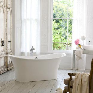 Imagen de cuarto de baño principal, romántico, grande, con armarios tipo mueble, puertas de armario grises, bañera exenta, sanitario de dos piezas, paredes blancas, suelo de madera pintada, lavabo sobreencimera, encimera de madera y suelo blanco