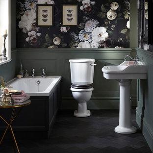 Modelo de cuarto de baño principal, clásico, con bañera encastrada, sanitario de dos piezas, paredes multicolor, suelo de madera oscura, lavabo con pedestal y suelo negro