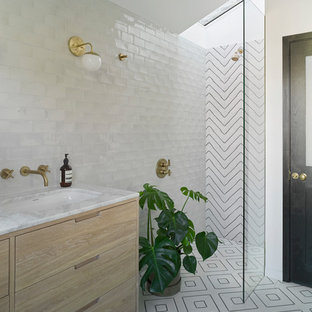 Photo of a contemporary bathroom in London with freestanding cabinets, light wood cabinets, black and white tiles, multi-coloured tiles, white tiles, a submerged sink, multi-coloured floors and an open shower.