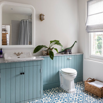 Elegant kids' mosaic tile floor and blue floor bathroom photo in London with beaded inset cabinets, granite countertops, blue cabinets, a one-piece toilet, white walls, a drop-in sink and gray countertops