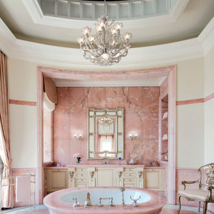 Victorian master bathroom in Los Angeles with raised-panel cabinets, beige cabinets, a freestanding tub, pink tile, beige walls, pink floor and pink benchtops.