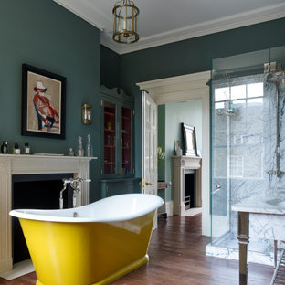 Medium sized victorian ensuite bathroom in London with a freestanding bath, a corner shower, a hinged door, white tiles, marble tiles, green walls, medium hardwood flooring and brown floors.