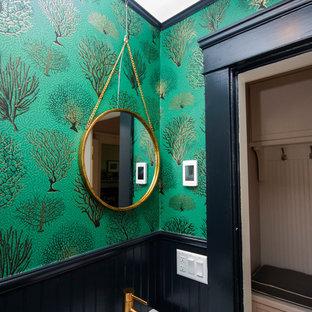 Foto på ett litet vintage badrum med dusch, med en toalettstol med separat cisternkåpa, gröna väggar, klinkergolv i porslin, ett väggmonterat handfat och svart golv