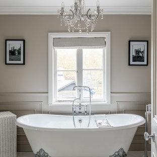 На фото: главная ванная комната среднего размера в классическом стиле с ванной на ножках, серыми стенами, тумбой под одну раковину, напольной тумбой, серым полом и панелями на стенах