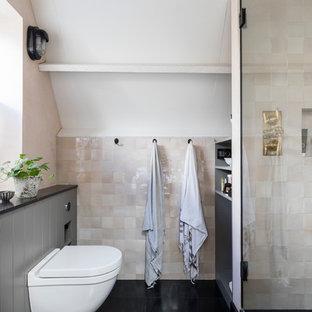 Modelo de cuarto de baño principal, urbano, con puertas de armario grises, ducha a ras de suelo, sanitario de pared, baldosas y/o azulejos rosa, paredes rosas, suelo de piedra caliza, encimera de piedra caliza, suelo negro, ducha con puerta con bisagras y encimeras negras