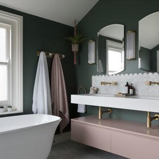 Modern inredning av ett mellanstort vit vitt en-suite badrum, med ett fristående badkar, en öppen dusch, en vägghängd toalettstol, gröna väggar, marmorgolv, bänkskiva i akrylsten och med dusch som är öppen
