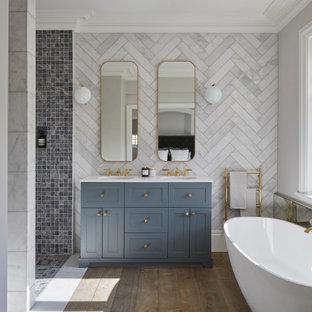 Imagen de cuarto de baño principal, tradicional renovado, con armarios estilo shaker, puertas de armario azules, bañera exenta, ducha a ras de suelo, paredes blancas, lavabo bajoencimera, suelo marrón, ducha abierta y encimeras blancas