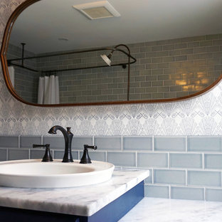 Ispirazione per una stanza da bagno padronale vittoriana di medie dimensioni con ante blu, vasca con piedi a zampa di leone, piastrelle grigie, piastrelle in ceramica, pareti grigie, pavimento con piastrelle in ceramica, top in marmo, pavimento grigio e top bianco
