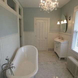 Cette photo montre une douche en alcôve principale victorienne de taille moyenne avec un placard avec porte à panneau surélevé, des portes de placard blanches, une baignoire sur pieds, un lavabo intégré, un carrelage de pierre, un mur blanc, un sol en marbre, un sol gris, un WC séparé, un carrelage blanc, un plan de toilette en surface solide, un plan de toilette blanc et une cabine de douche à porte battante.
