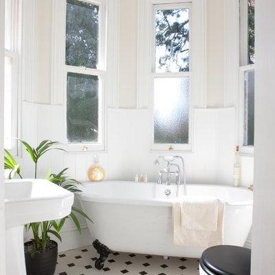 Small elegant claw-foot bathtub photo in Surrey with pink walls