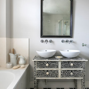 Photo of a small mediterranean bathroom in Hampshire with white walls, a vessel sink, multi-coloured floors, multi-coloured worktops, freestanding cabinets, black cabinets and a built-in bath.
