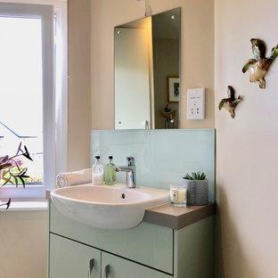 Foto di una piccola stanza da bagno con doccia chic con ante lisce, ante verdi, doccia aperta, WC monopezzo, piastrelle verdi, lastra di vetro, pareti beige, pavimento in vinile, lavabo da incasso, top in laminato, pavimento verde, porta doccia scorrevole e top grigio