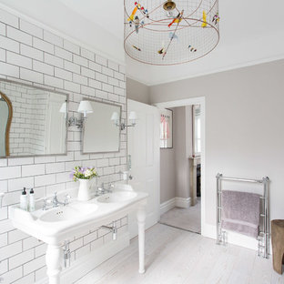 Inspiration for a contemporary ensuite bathroom in London with open cabinets, white cabinets, beige walls, a console sink and light hardwood flooring.
