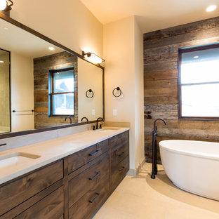 Modelo de cuarto de baño principal, rural, grande, con bañera exenta, paredes blancas, encimera de cuarcita, armarios con paneles lisos, puertas de armario de madera en tonos medios, suelo de baldosas de cerámica y lavabo bajoencimera