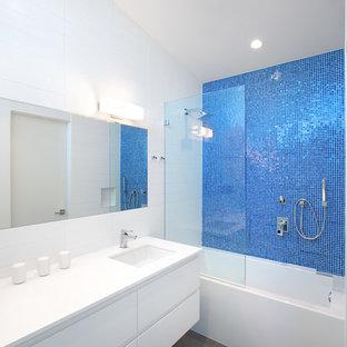 バンクーバーのコンテンポラリースタイルのおしゃれな浴室 (アンダーカウンター洗面器、フラットパネル扉のキャビネット、白いキャビネット、珪岩の洗面台、壁掛け式トイレ、青いタイル、モザイクタイル、白い壁、磁器タイルの床、アルコーブ型浴槽、シャワー付き浴槽) の写真
