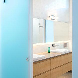 Modelo de cuarto de baño minimalista con armarios con paneles lisos, puertas de armario de madera clara, encimera de cuarcita, sanitario de pared, baldosas y/o azulejos de porcelana, paredes blancas, suelo de baldosas de porcelana y baldosas y/o azulejos blancos
