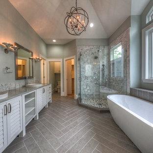 Inredning av ett klassiskt stort en-suite badrum, med luckor med lamellpanel, vita skåp, ett fristående badkar, en hörndusch, vit kakel, marmorkakel, grå väggar, laminatgolv, ett nedsänkt handfat, bänkskiva i kvarts, brunt golv och dusch med gångjärnsdörr