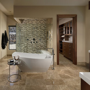Inspiration for a southwestern brown floor freestanding bathtub remodel in Las Vegas with flat-panel cabinets, dark wood cabinets, beige walls, a vessel sink, a hinged shower door and white countertops