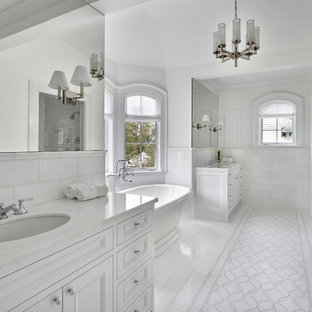 Mediterranean ensuite bathroom in Chicago with white cabinets, a freestanding bath, white tiles, white walls, marble flooring, white floors, a hinged door, recessed-panel cabinets, an alcove shower, metro tiles, a submerged sink and white worktops.