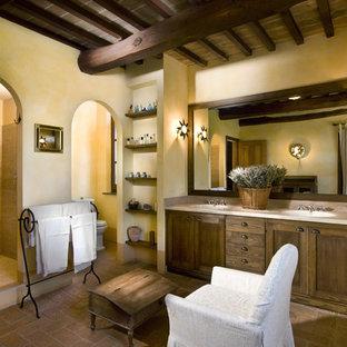 Неиссякаемый источник вдохновения для домашнего уюта: огромная главная ванная комната в средиземноморском стиле с темными деревянными фасадами, накладной ванной, душем в нише, бежевой плиткой, кирпичным полом, желтыми стенами, монолитной раковиной, мраморной столешницей и фасадами в стиле шейкер