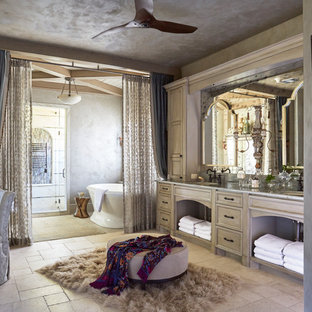 Inspiration for a mediterranean beige floor freestanding bathtub remodel in Houston with recessed-panel cabinets, light wood cabinets and an undermount sink